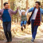 gay-male-couple-with-daughter-walking-through-fall-woodland-picture-id514319092