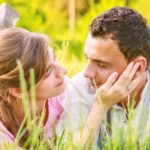 Close-up of a young couple in love on grass