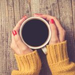 female-hands-in-warm-sweater-holding-cup-of-coffee-picture-id868707272