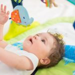 baby-boy-lying-on-back-and-playing-with-toys-picture-id656339092