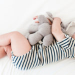 Baby wearing striped onesie sleeping with a stuffed animal