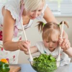 Blond mother and child cooking in kitchen