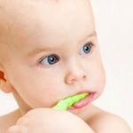 Little baby girl with green tooth brush