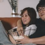 asian-chinese-couple-watching-tv-show-at-night-during-weekend-in-picture-id993346792