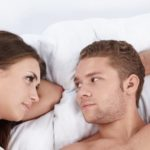Young attractive couple in bed with a condom