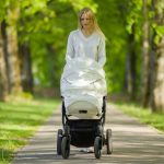 one-young-mother-pushing-white-baby-stroller-and-slowly-walking-of-picture-id1246921575