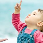 baby-in-denim-sits-on-the-beach-and-looks-up-picture-id1145518928