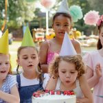 down-syndrome-child-with-friends-on-birthday-party-outdoors-in-garden-picture-id1206670400
