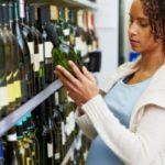 Pregnant woman with bottle of wine at super market