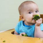beautiful baby eating broccoli