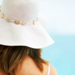 beach woman wearing a hat from behind