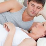 Worried pregnant woman lying on bed with her husband at home