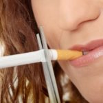 Young woman quiting smoking – focus on hand