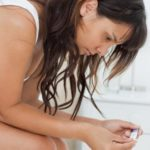 Worried young woman looking a pregnancy test