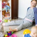 tired-of-everyday-household-mother-sitting-on-floor-with-hands-on-picture-id1143719115