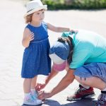 father-helping-his-little-daughter-with-her-shoes-picture-id898458136