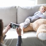 a-toddler-poses-for-a-picture-with-a-big-teddy-bear-picture-id1175554407