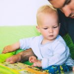 little-boy-is-reading-a-book-with-his-father-in-a-home-interiors-picture-id669407038