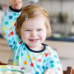 adorable-baby-girl-eating-from-spoon-vegetable-noodle-soup-food-child-picture-id936817244