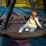 two-toddlers-a-boy-and-a-girl-play-cheerfully-and-swing-on-a-swing-picture-id1260031028
