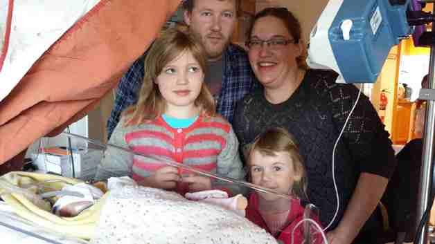 Pappa Martin, mamma Anja, Malin og Sunniva sammen med Sofie i sengen.