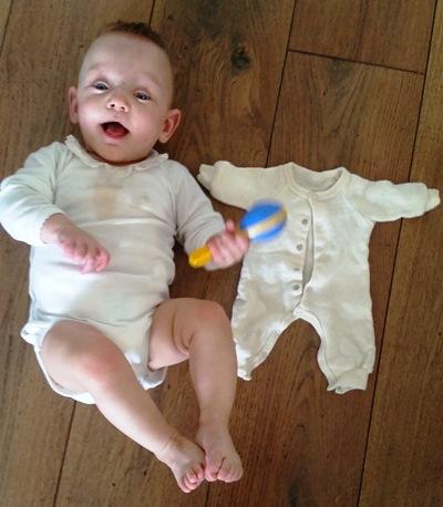 Sofie 11 måneder gammel, ved siden av dressen som var for stor da hun var to måneder.