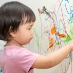 little-baby-girl-drawing-with-crayon-color-on-the-wall-picture-id1255570988