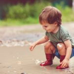 little-boy-playing-in-puddle-in-a-rainy-day-picture-id1143257702