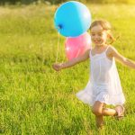 happy-cheerful-girl-playing-and-having-fun-with-balloons-picture-id509205067