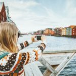 tourist-woman-taking-photo-by-smartphone-sightseeing-in-norway-picture-id1211329136