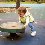 cute-toddler-kid-plays-fun-on-the-playground-in-the-autumn-park-picture-id1265214300