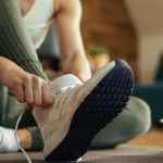 closeup-of-athletic-woman-putting-on-sneakers-picture-id1210120932