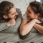 young-couple-laying-down-in-bed-picture-id1276127212