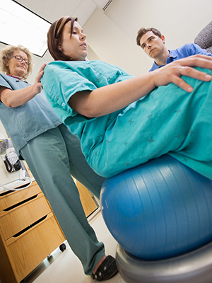 Å sitte og vugge på en pilatesball kan være en god fødestilling. Illustrasjonsfoto: Shutterstock