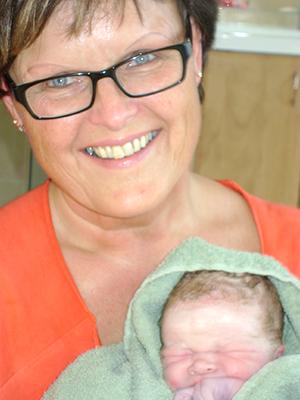 Jordmor Grethe med en ny liten verdensborger kommet trygt til verden hjemme. Foto: jordmor Ragna T. Larsen
