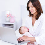 Mother with baby using laptop in room