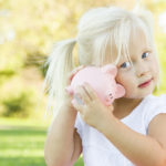 Little Girl Having Fun with Her Piggy Bank Outdoors