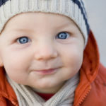 Close-up of a cute smiling blue-eyed baby boy with knit hat