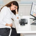 Upset Pregnant Woman Sitting At Computer Desk