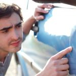 young-man-looking-for-scratches-on-his-car-picture-id4822130971