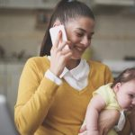 mother-working-at-home-mother-holding-her-little-baby-in-arms-picture-id8577955861