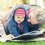 mother-and-little-baby-girl-reading-book-together-on-blanket-outdoors-picture-id820953278