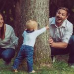 happy-family-with-a-cute-baby-playing-hide-and-seek-in-the-woods-picture-id1284958758