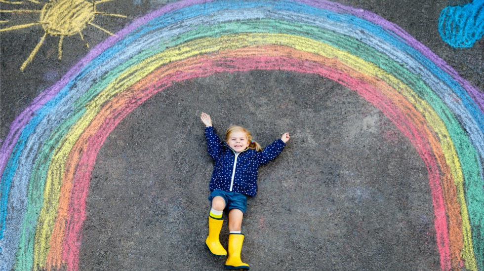 happy-little-toddler-girl-in-rubber-boots-with-rainbow-sun-and-clouds-picture-id1199911464