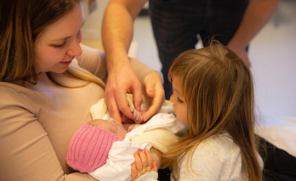 Storesøster ønsket ikke å holde lillesøster selv, men var nysgjerrig på den lille. Foto: Trine-Lise Henriksen