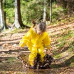 cute-little-girl-jumping-in-muddy-puddle-picture-id840614644
