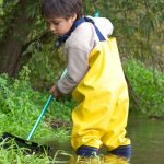 young-boy-and-his-net-fishing-in-a-stream-picture-id182246588