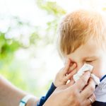 little-boy-having-allergy-problems-in-nature-picture-id975115022