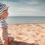 little-baby-boy-sitting-on-the-beach-in-summer-day-picture-id1271581374
