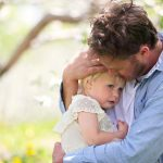 father-holding-and-comforting-sad-baby-daughter-picture-id809056466